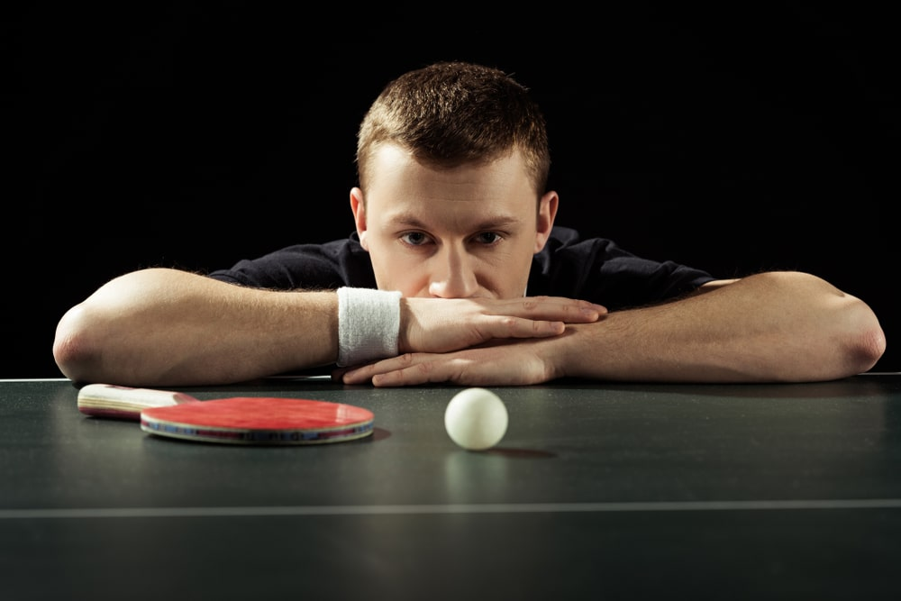 portrait of thoughtful tennis player at tennis table with ball and racket