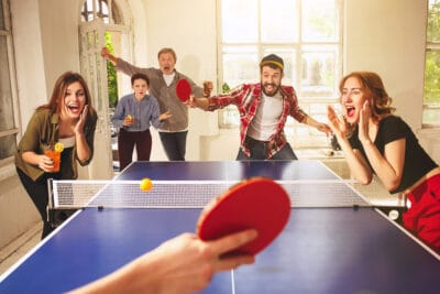Group of happy young friends playing ping pong