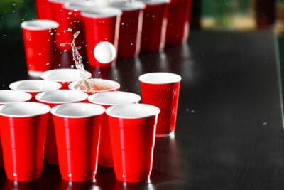 Cups and plastic ball for beer pong game on table