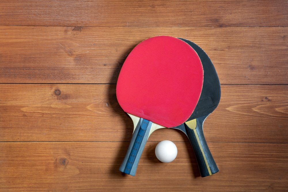Two ping-pong rackets and a ball on a brown wooden background, close-up