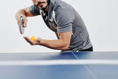 Cropped image of bearded ping pong player serving ball
