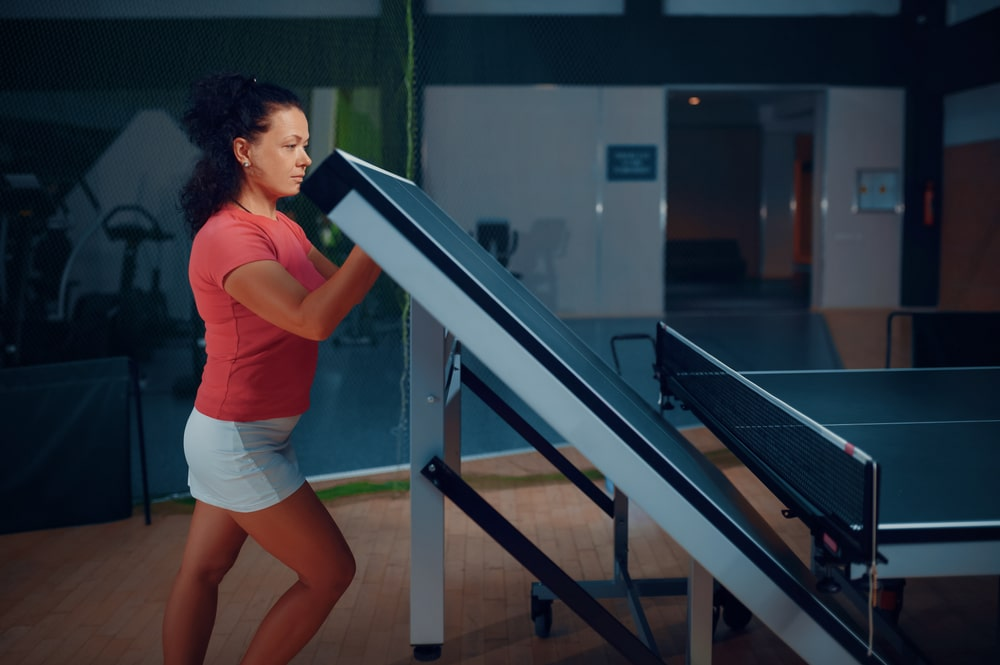 Woman folds ping pong table