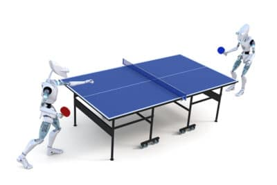 Two robots playing a game of table tennis against a white background.