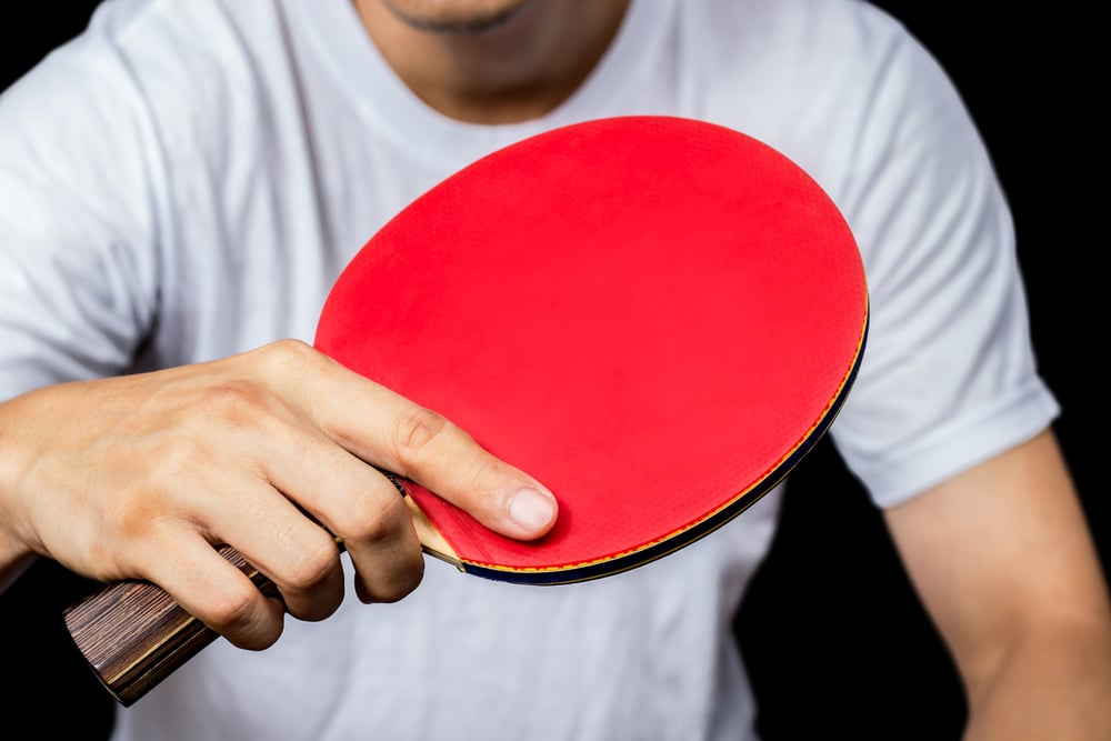 player holding red pingpong or table tennis rack in hand