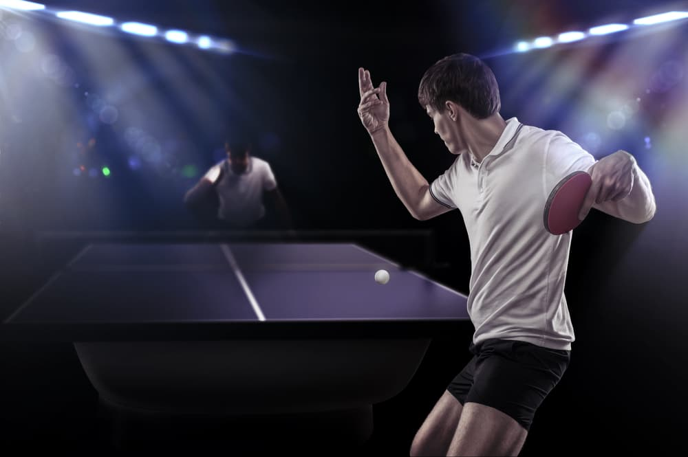 Table tennis player is making a service