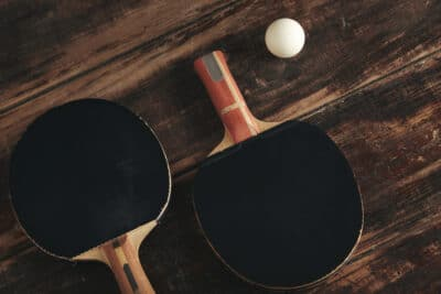 Two professional ping pong rockets lying on vintage wooden table.