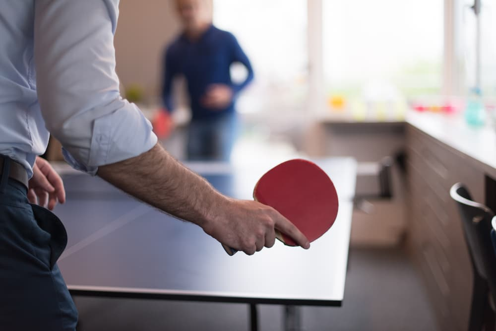 business people playing ping pong tennis at modern creative office