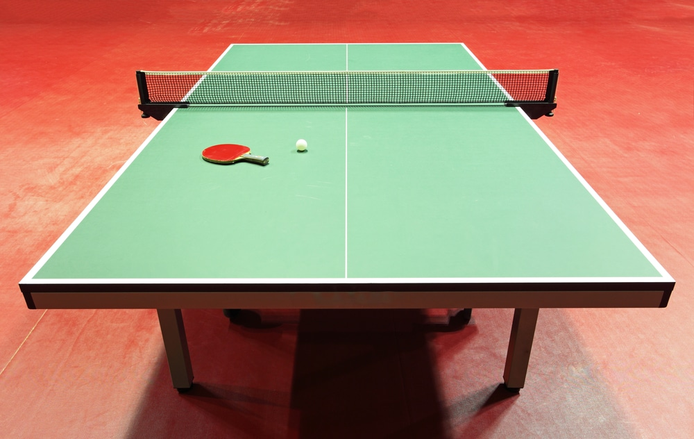 A ping pong table on a red floor.