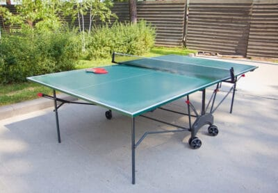 Green ping-pong table and rackets outdoor