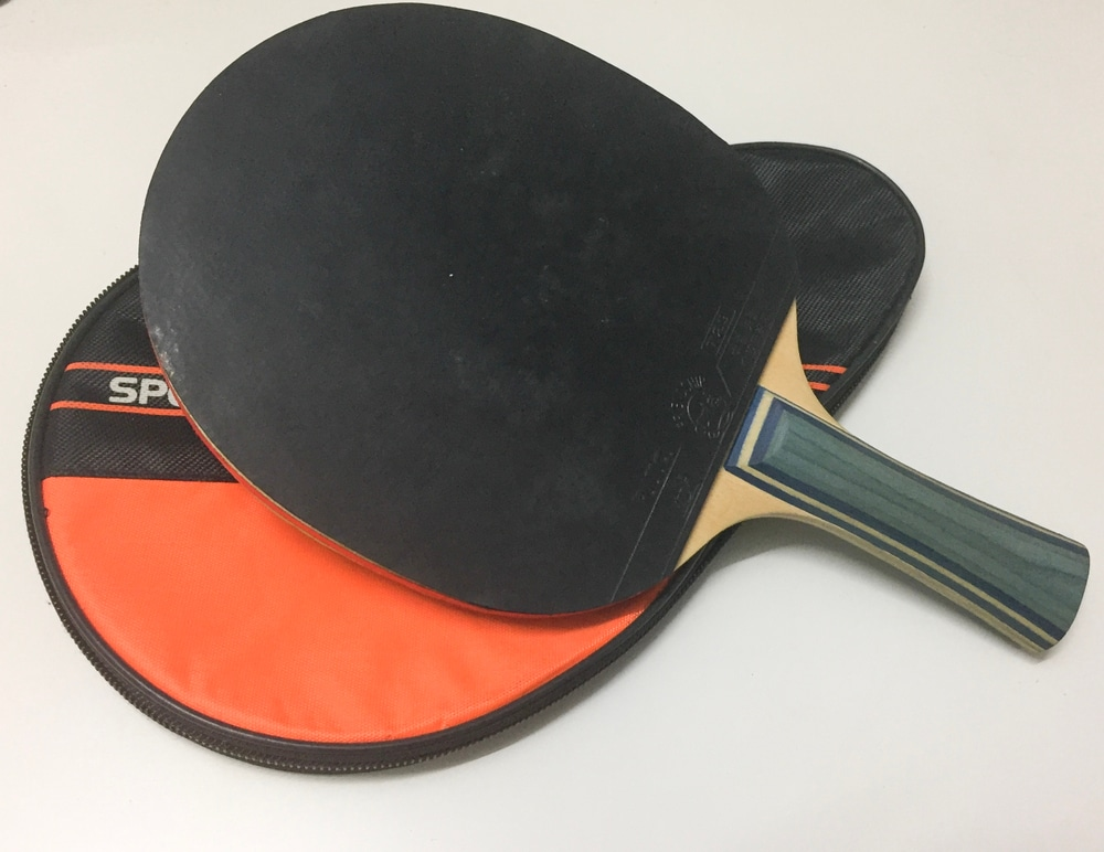 racket with rubber handle for table tennis with case lying on the white table
