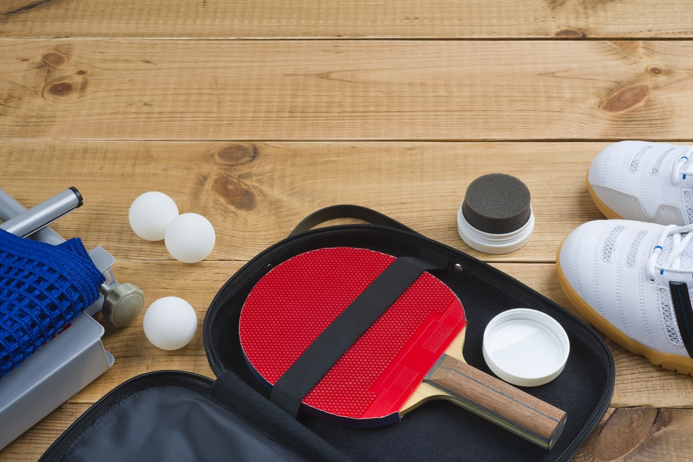 Table tennis paddle in open case next to a pair of shoes