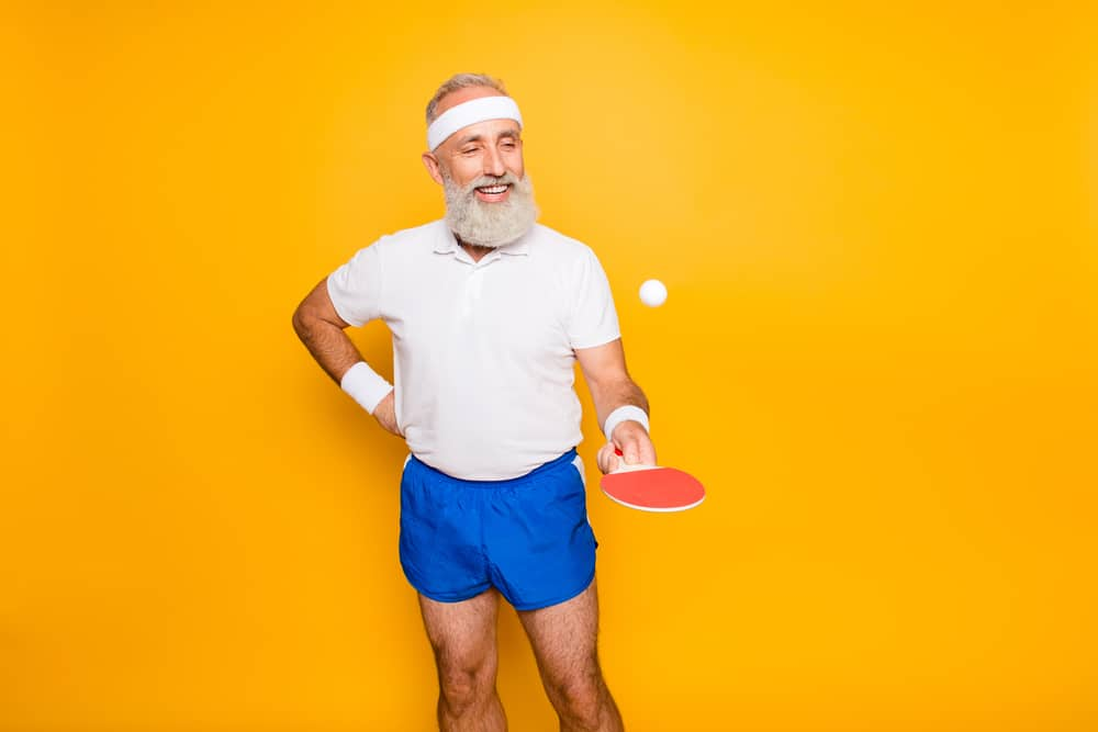 grandpa with beaming grin, with table tennis equipment