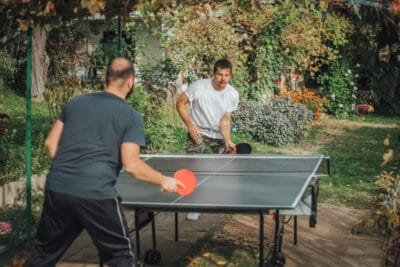Colleagues having fun in the backyard while playing table tennis