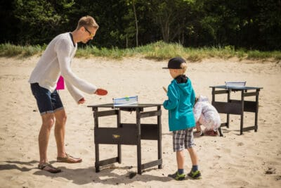Father and son playing Mini Ping Pong Table game by the beach