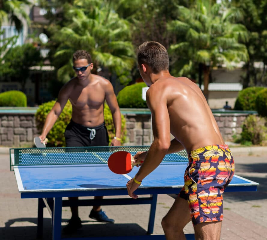 young men playing table tennis outdoors