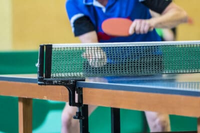 table tennis player serving, focus at the net, player in the background