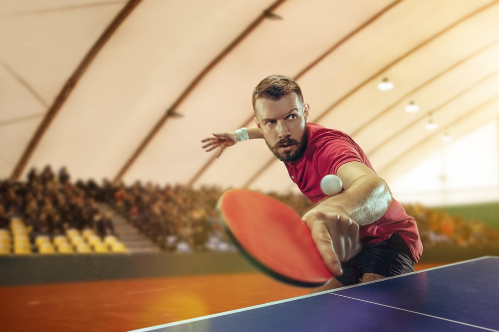 Fit young man playing ping pong in a sport arena