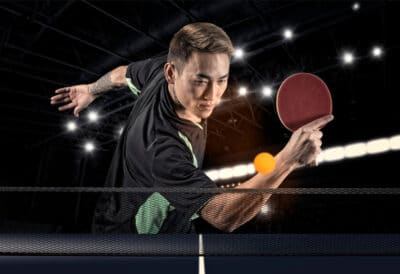 Man playing tennis on dark background with lights
